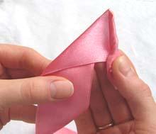 1. Оставьте небольшой кончик и начинайте заворачивать ленту вокруг пальца по диагонали. Заверните ленту в три оборота и закрепите лентой. Получилась сердцевинка розы. Зафиксируйте нитку, не отрезайте её, мы будем продолжать работу с остатком нити.